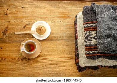Cup of tea and pile of sweaters, top view