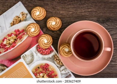 Cup of tea in pink mug and biscuits with magazine