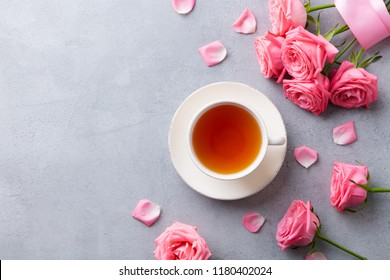 Cup of tea with pink rose. Top view. Copy space. Grey stone background.