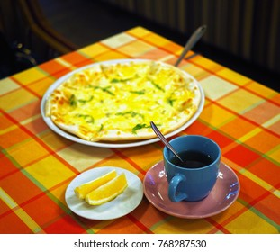 a cup of tea, pizza and lemon slices on a table with a checkered tablecloth