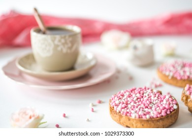 cup of tea and rusk with traditional Dutch food pink muisjes, aniseed, for celebration birth of a daughter, blur background