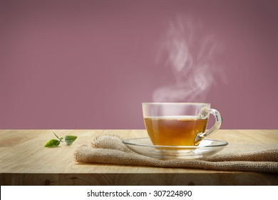 Cup of tea with sacking on the wooden table and pink background