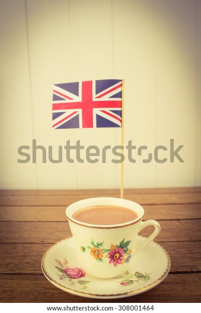 A cup of tea served in a traditional cup and saucer with an British flag on a wooden table top