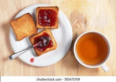 Cup of tea and small toast bread with jam in a plate on a wooden table, top view