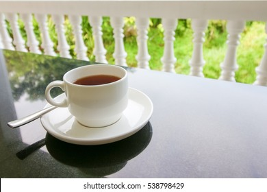 cup of the tea with spoon and plate on the black table