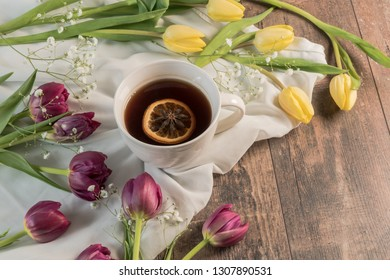 Cup of tea surrounded by tulips
