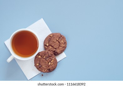 Cup of tea and tasty chocolate cookies with nuts on the blue table, top view with space for text