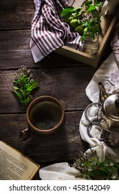 Cup of tea, teapot and book on dark wooden background. Style rustic. Selective focus.