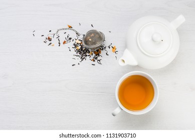 cup of tea with teapot and closed infuser with black tea on table