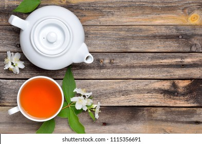 Cup of tea, teapot and jasmine flowers on rustic wooden table, Flat lay, top view. Copispace background.