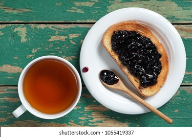 Cup of tea and toasted bread with blueberry jam in plate on old green wooden table, top view