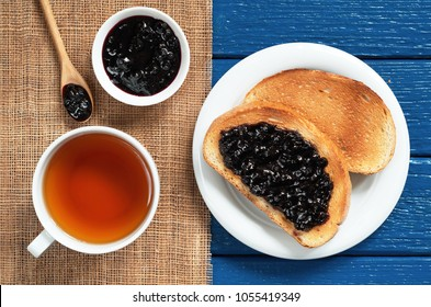 Cup of tea and toasted bread with blueberry jam for breakfast on the blue wooden table, top view