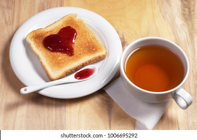 Cup of tea and toasted bread with strawberry jam in the shape of heart in plate on the wooden table