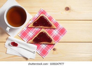 Cup of tea and toasted bread with tasty jam on the wooden table, top view with space for text