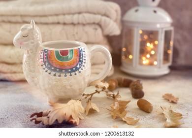 Cup of tea in trendy llama shape mug autumn leaves white wool sweater