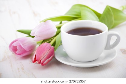 A cup of tea with tulips on a white wooden background