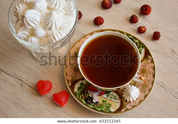 A cup of tea and a vase with meringue