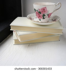 Cup of tea in a vintage china cup and saucer on top of a stack of hardback books on a windowsill. Square photo.