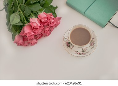 Cup of tea in vintage cup and saucer, journal and pink roses
