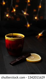 Cup of tea with water drops falling into the cup on dark background with Christmas lights, sweet chokolate and sour lemon nearby