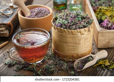 Cup of tea with wild Marjoram and Erica flowers. Dry Origanum vulgare and heather medicinal plants, old book and bottles of essential oil on background.