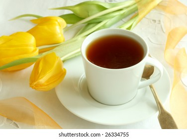 Cup of tea and yellow tulips