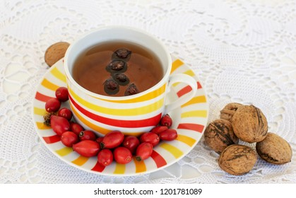 Cup of team made from Rosa canina seeds and walnuts placed on a embroidered tablecloth.