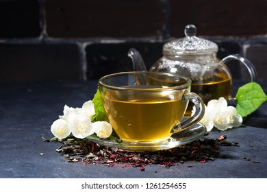 cup and teapot of fragrant jasmine tea on a dark background, closeup horizontal