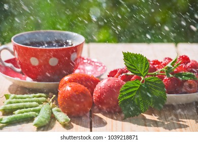 A Cup of tea,tomatoes, pea pods and raspberries in a saucer on a wooden table in drops of summer rain.