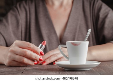 Cup of tested coffee with track of red lipstick