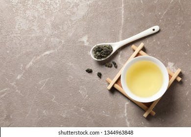 Cup of Tie Guan Yin oolong and spoon with tea leaves on table, top view. Space for text
