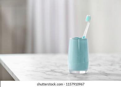 Cup with toothbrush on table. Dental care