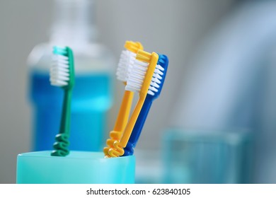 Cup with toothbrushes on blurred background