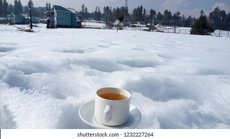 A cup of traditional tea 'Kashmiri Kahwa' on a winter morning with enjoying fresh snow in Yusmarg, Kashmir,  India. Christmas and New Year celebration in Kashmir, India.