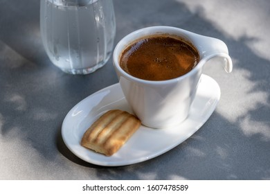 Cup of traditional Turkish coffee served with one biscuit and glass of water on a sunny day