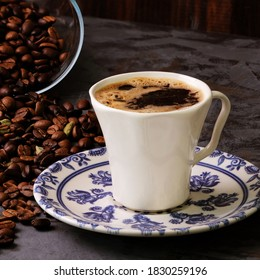 A cup of Turkish coffee with a background of roasted coffee beans