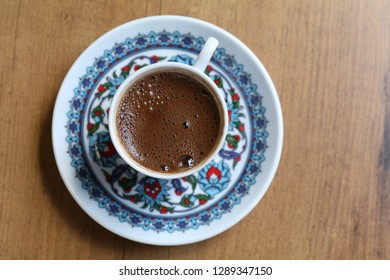 a cup of turkish coffee on a wooden table
