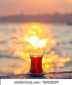 A cup of Turkish tea against the backdrop of the sunset and the Bosporus Strait. Turkey, Istanbul