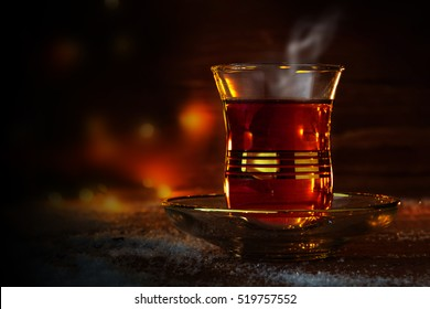 Cup of Turkish tea on saucer on rustic wood with snow in front of a dark blurred background with red and golden bokeh lights, copy space, selected focus, narrow depth of field