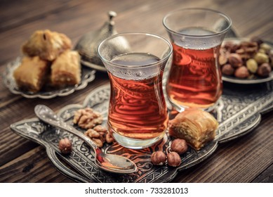 Cup of turkish tea served in traditional style with turkish delay on wooden background
