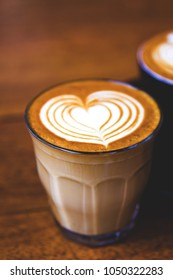 Cup of two hot cappucino are the wooden table. Heart is an art on one latte