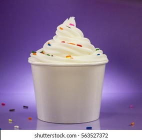 Cup of Vanilla Frozen Yogurt with Sprinkles Against a Purple Background