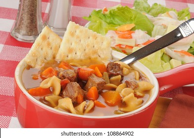 A cup of vegetable beef soup with crab salad in the background