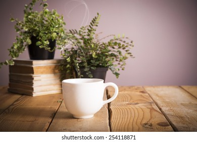 A cup of warm coffee and ferns on top of books