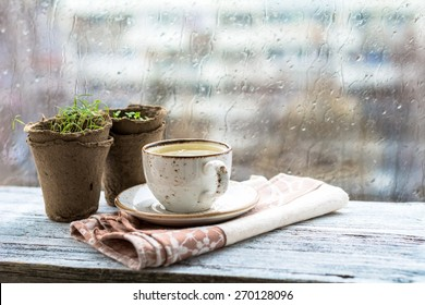 Cup with warm drink on wooden table in front of window with rain drops, rainy weather. Moody still life. Warm tones, horizontal image