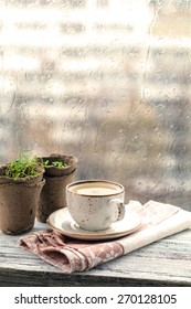Cup with warm drink on wooden table in front of window with rain drops, rainy weather. Moody still life. Warm tones, vertical image