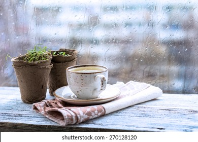 Cup with warm drink on wooden table in front of window with rain drops, rainy weather. Moody still life. Cold tones, horizontal image