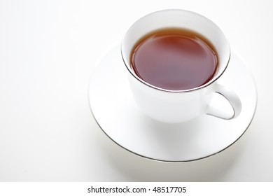 A cup of warm tea on white background. Plenty of copy space.