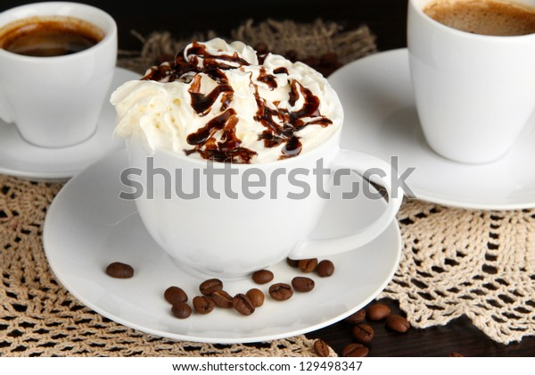 Cup of whipped cream coffee on wooden table close up
