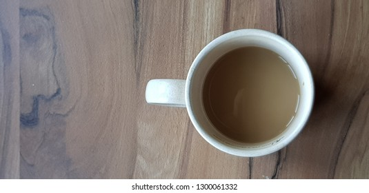 A cup of white coffee on the wooden table with natural light from window